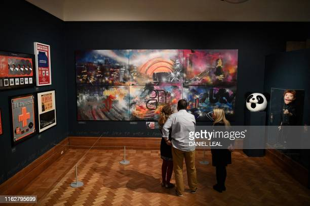 Visitors look at an image painted as a birthday present for British musician Ed Sheeran by the artist Graham Dews during a press preview of the...