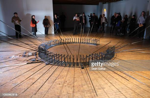 Visitors look at an installation that uses radio waves to determine the movement of metal rods at 'Bauhaus 100 Years The Opening Festival' during a...