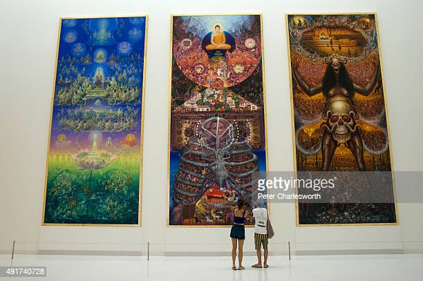 Visitors look at an installation three huge commissioned paintings about Buddhism and materialism inside the sixstory Museum of Contemporary Art or...