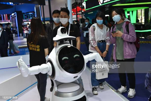 Visitors look at an intelligent robot during China International Big Data Industry Expo at Guiyang International Conference and Exhibition Center on...