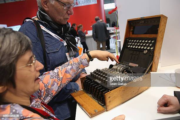Visitors look at an original World War II Enigma coding machine at the stand of the German Federal Intelligence Service at the 2015 CeBIT technology...