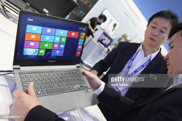 Visitors look at an ultra thin Samsung Notebook Series 9 laptop computer during a press day at the Samsung stand at the IFA 2012 consumer electronics...