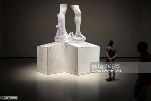 TOPSHOT Visitors look at an untitled sculpture by Argentinian sculptor Adrian Villar Rojas at the Louis Vuitton foundation on August 23 2018 in Paris...