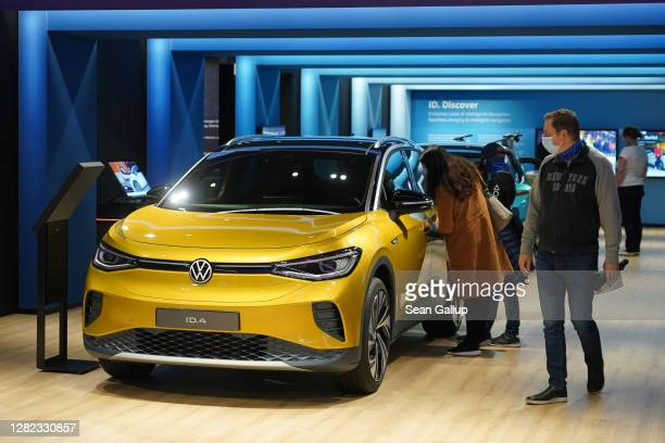 Visitors look at an Volkswagen ID.4 electric car at the Autostadt promotional facility next to the Volkswagen factory on October 26, 2020 in...