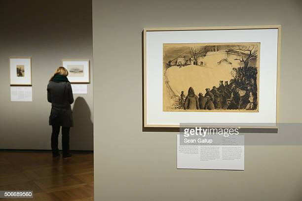 Visitors look at artworks by Holocaust victims including the work The Funeral by Leo Haas that he drew while an inmate at the Theresienstadt ghetto...