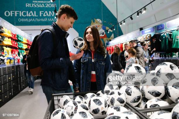 ed1245fab62 Visitors look at balls at the official shop of the FIFA Fan Fest in Moscow  on