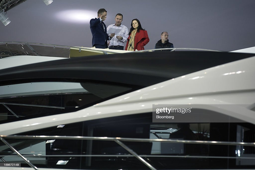 Visitors look at boats on display from the bridge of a Sunseeker International Ltd. luxury yacht during the Tullet Prebon London Boat Show 2013 at the ExCeL center in London, U.K., on Wednesday, Jan. 16, 2013. The show, Europe's first in 2013, will showcase new sailing craft from dinghies to luxury yachts, and runs Jan. 12-20. Photographer: Simon Dawson/Bloomberg via Getty Images