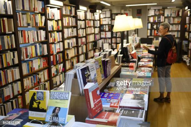 Visitors look at books displayed at Le Failler bookshop as part of the autumn literary season on September 5 2017 in Rennes western France / AFP...
