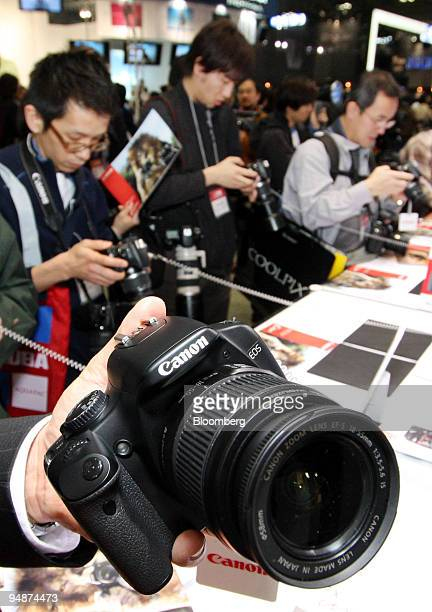 Visitors look at Canon Inc's EOS digital cameras displayed at the Photo Imaging Expo 2008 in Tokyo Japan on Wednesday March 19 2008 Canon Inc is the...