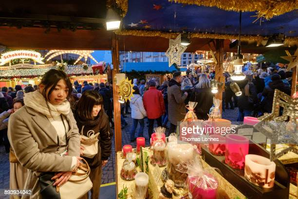 Visitors look at Christmas decorations and candles at the annual Christmas market at Roemerberg on December 16 2017 in Frankfurt Germany Christmas...