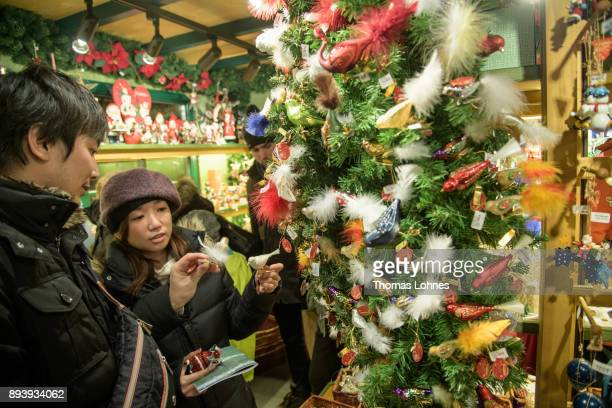 Visitors look at Christmas decorations at the annual Christmas market at Roemerberg on December 16 2017 in Frankfurt Germany Christmas markets are an...