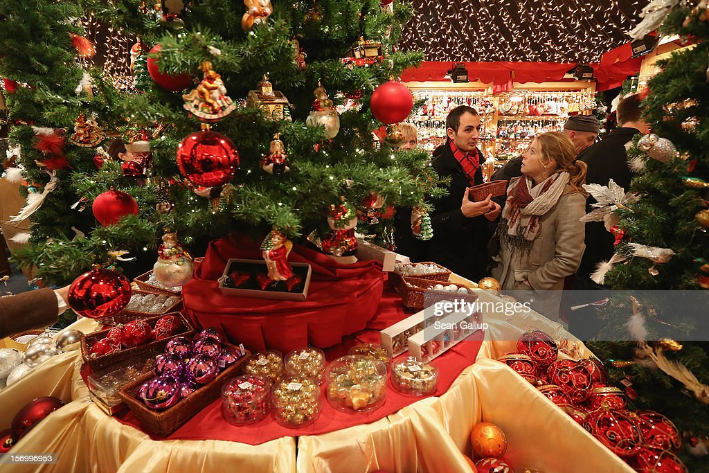 Visitors look at Christmas decorations for sale at the Kaethe Wohlfahrt stand at the annual Christmas market at Gendarmenmarkt on its opening day on November 26, 2012 in Berlin, Germany. Christmas markets, with their stalls selling mulled wine, Christmas tree decorations and other delights, are an integral part of German Christmas tradition, and many of them opened across Germany today.