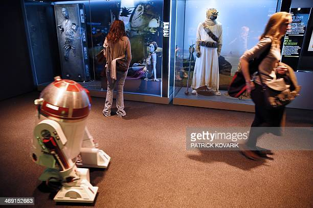 Visitors look at costumes of character from the Star Wars film series, as a model of a droid drives past, during the presentation of the exhibition...