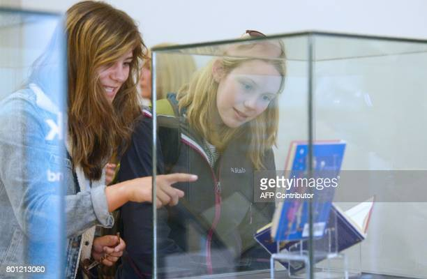 Visitors look at dandwritten notes by author JK Rowling written inside a rare first edition of her book 'Harry Potter and the Philosopher's Stone'...