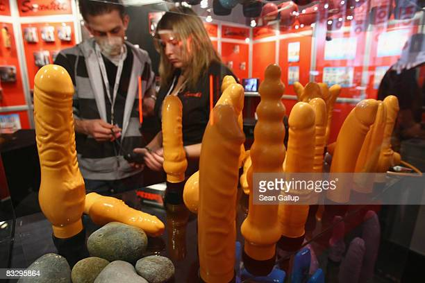 Visitors look at dildos at the Venus Erotic Trade Fair during its industry professionals' day on October 16 2008 in Berlin Germany The Venus fair...