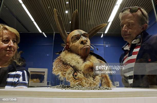 Visitors look at 'El Neandertal Emplumado' a scientificly based impression of the face of a Neanderthal who lived some 50000 years ago by Italian...