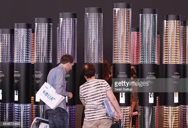 Visitors look at espresso coffee capsules at the Nespresso stand at the 2014 IFA home electronics and appliances trade fair on September 5 2014 in...