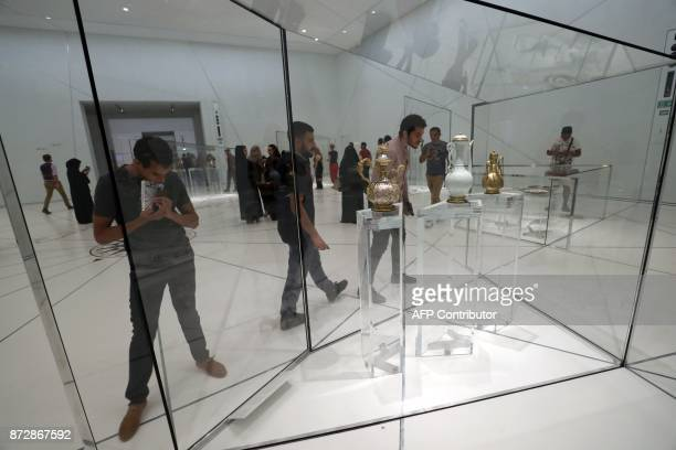 Visitors look at exhibits during the opening of the Louvre Abu Dhabi Museum on November 11 2017 on Saadiyat island in the Emirati capital / AFP PHOTO...