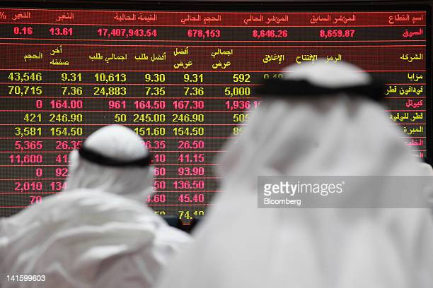 Visitors look at financial information screens on display inside the Qatar Exchange in Doha Qatar on Saturday March 17 2012 The country the biggest...