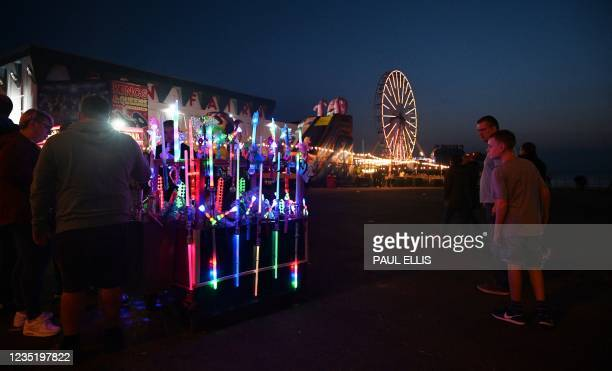 Visitors look at flourescent toys on the promenade in Blackpool, north west England on September 4, 2021. - Blackpool's Illuminations lights festival...