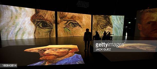 Visitors look at giant screens featuring images of the work of Dutch painter Vincent van Gogh during a traveling multimedia art exhibition entitled...