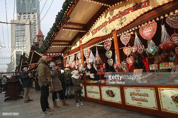 Visitors look at gingerbread hanging at a food stand that reopened moments before at the Breitscheidplatz Christmas market only a short distance from...