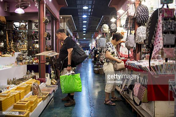 Visitors look at handicrafts and other merchandise at Asiatique The Riverfront openair mall in Bangkok Thailand on Friday Dec 18 2015 Thai economic...