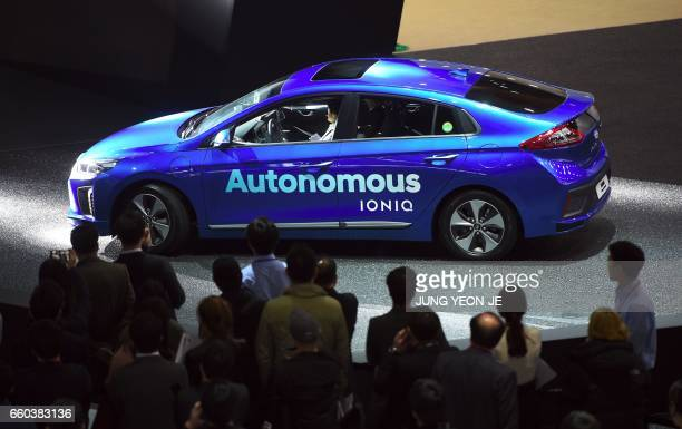 Visitors look at Hyundai Motor's Autonomous Ioniq car during a press preview of the Seoul Motor Show in Goyang northwest of Seoul on March 30 2017...