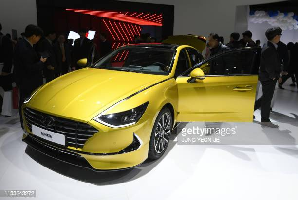 Visitors look at Hyundai Motor's Sonata during a press preview of the Seoul Motor Show in Goyang northwest of Seoul on March 28 2019 South Korea's...