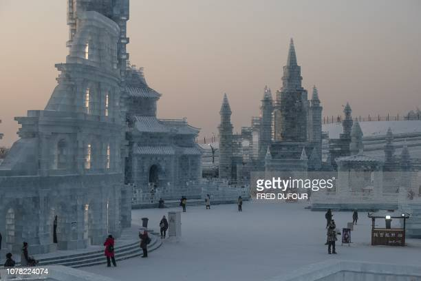 Visitors look at ice sculptures during the annual Harbin Ice and Snow Festival in Harbin in China's northeast Heilongjiang province on January 6 2019