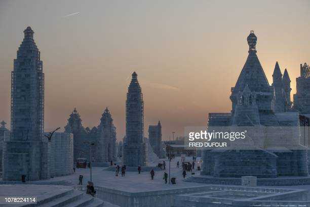 TOPSHOT Visitors look at ice sculptures during the annual Harbin Ice and Snow Festival in Harbin in China's northeast Heilongjiang province on...