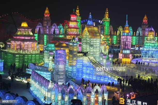 Visitors look at ice sculptures during the opening of the 30th Harbin International Ice Snow Sculpture Festival on January 5 2014 in Harbin...