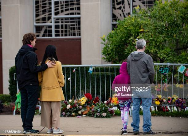 Visitors look at items well-wishers have left behind along the fence at the Tree of Life Synagogue on the 1st Anniversary of the attack on October...