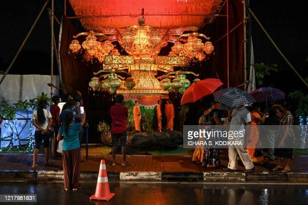 Visitors look at lanterns displayed near Sri Lanka's military headquarters in the capital Colombo on June 6 a day after the Poson Poya religious...