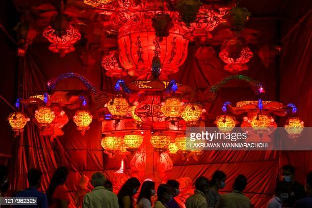 TOPSHOT Visitors look at lanterns displayed near Sri Lanka's military headquarters in the capital Colombo on June 6 a day after the Poson Poya...