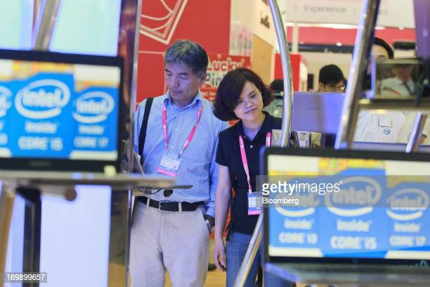 Visitors look at laptops at the Intel Corp booth at Computex Taipei 2013 in Taipei Taiwan on Tuesday June 4 2013 Computex Asia's biggest...