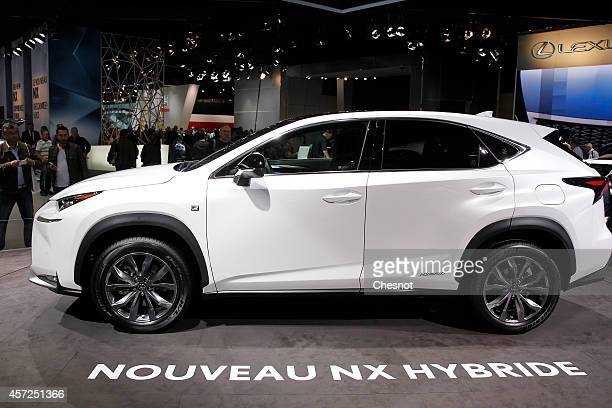 Visitors look at Lexus NX hybrid automobile during the Paris Motor Show on October 14 2014 in Paris France More than a million visitors are expected...
