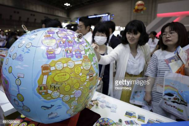 """Visitors look at MegaHouse Corp.'s board game """"Chikyu Maruboto Sugoroku"""" at the International Tokyo Toy Show in Tokyo, Japan, on Thursday, June 1,..."""
