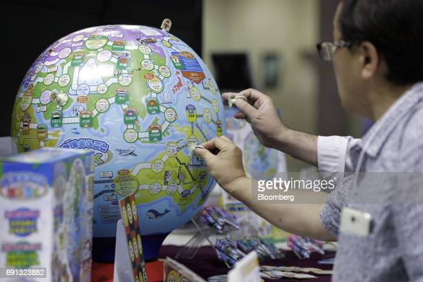 Visitors look at MegaHouse Corp.'s board game 'Chikyu Maruboto Sugoroku' at the International Tokyo Toy Show in Tokyo, Japan, on Thursday, June 1,...