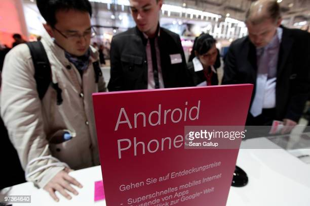Visitors look at mobile phones using the Android operating system at the Deutsche Telekom stand at the CeBIT Technology Fair on March 2 2010 in...