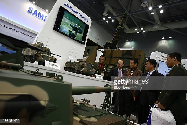 Visitors look at models of Samsung Techwin Co. Tanks at the Seoul International Aerospace & Defense Exhibition 2013 in Goyang, South Korea, on...