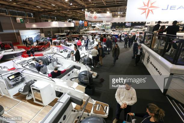 Visitors look at motorboats of the French yacht manufacturer Jeanneau during the Paris International Boat Show on December 9 2018 at the Porte de...