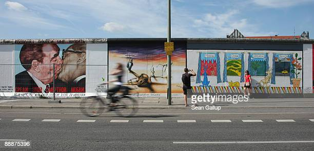 Visitors look at murals that decorate a surviving portion of the Berlin Wall known as the East Side Gallery on July 7 2009 in Berlin Germany The...