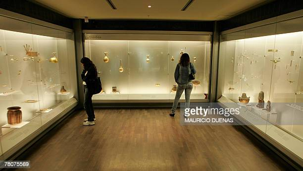 Visitors look at objects on display at the Gold Museum in Bogota Colombia on November 16th 2007 The museum keeps one of the most important...