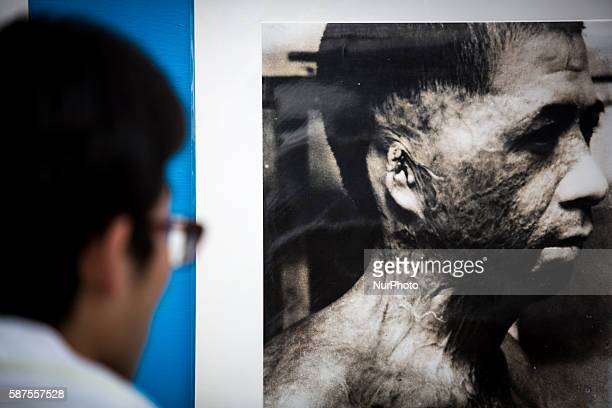 Visitors look at old photos of atomic bomb victims exhibited at Nagasaki Peace Park in Nagasaki during the 71st anniversary of the atomic bombing on...