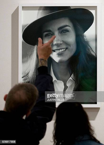 Visitors look at one of two new portraits of Catherine, Duchess of Cambridge, taken in the Norfolk Countryside by British photographer Josh Olins, at...