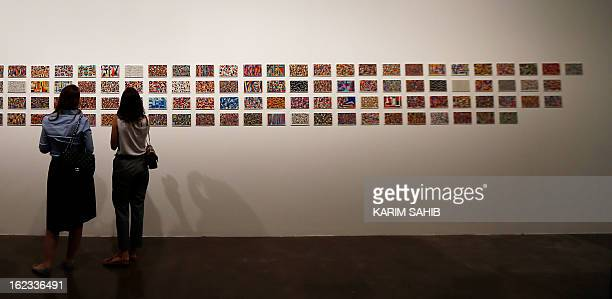 Visitors look at paintings by Emirati digital artist Ebtisam Abdulaziz on display during part of an exhibition titled Autobiography 2012 in Dubai on...