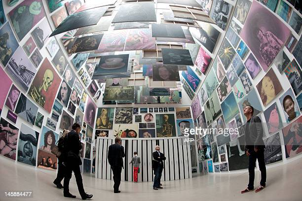 Visitors look at paintings displayed in the installation 'Limited Art Project 20112012' consisting of 377 paintings commissioned and produced by...