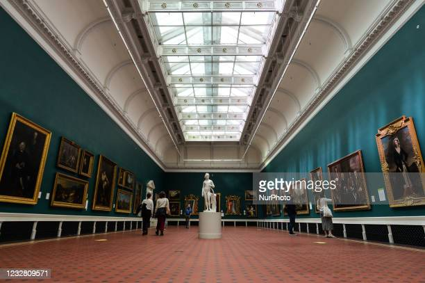 Visitors look at paintings inside the National Gallery of Ireland in Dublin. After five months of strict lockdown, the first stage of defrosting the...