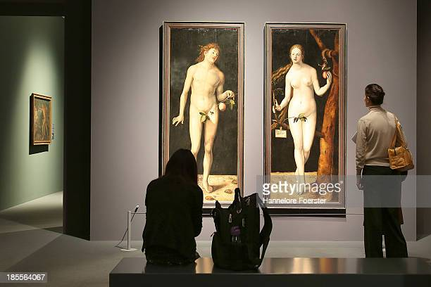 Visitors look at paintings of Adam and Eve at the Albrecht Durer exhibition in the Staedel museum on October 22 2013 in Frankfurt am Main Germany